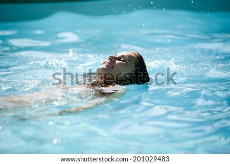 cheerful beautiful young woman in resort swimming pool during summer vacations - stock photo