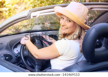 Cheerful beautiful young woman in the car. - stock photo