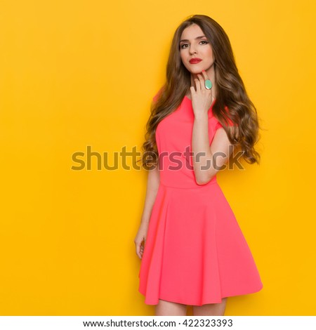 Cheerful beautiful young woman with curly long brown hair posing in pink mini dress and holding hand on chin. Three quarter length studio shot on yellow background. - stock photo