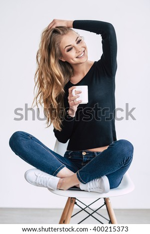 Cheerful beauty. Beautiful young woman holding coffee cup and looking away with smile while sitting on chair in lotus position against white background  - stock photo