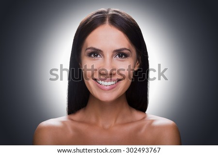 Cheerful beauty. Portrait of smiling young shirtless woman looking at camera while standing against grey background - stock photo