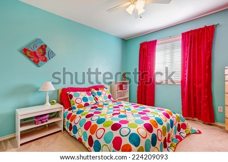 Cheerful bedroom interior in turquoise color with bright red curtains and colorful bedding - stock photo