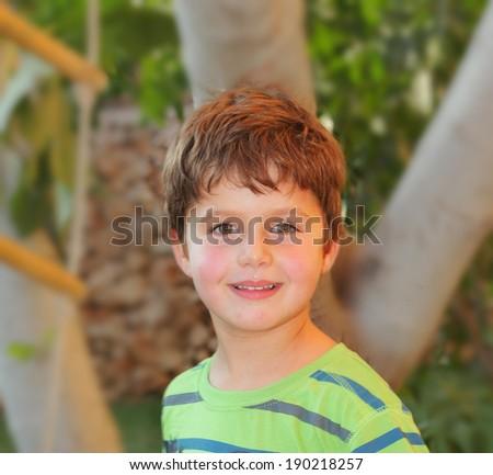 Cheerful birthday charming little boy in the park. Boy having fun smiling - stock photo