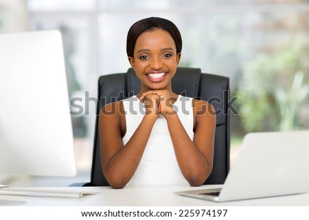 cheerful black businesswoman in modern office - stock photo