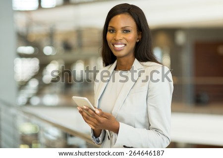 cheerful black businesswoman with smart phone in modern office - stock photo
