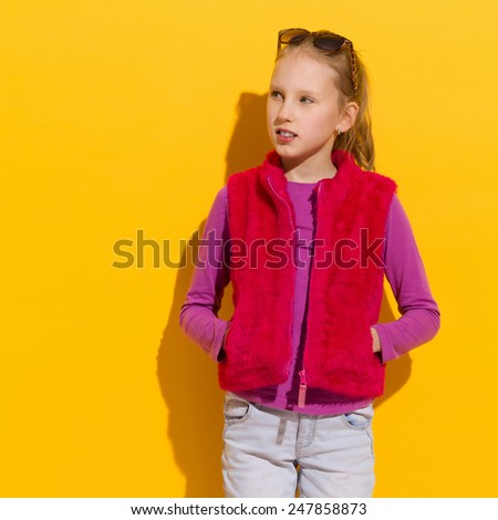 Cheerful blond girl in pink fur vest posing with hands in pockets. Waist up studio shot on yellow background. - stock photo