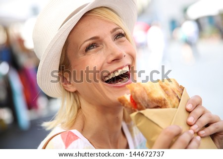 Cheerful blond girl in Rome eating Focaccia sandwich - stock photo