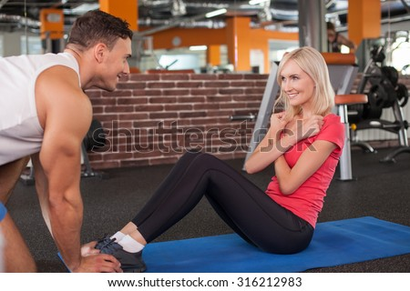 Cheerful blond girl is doing sit-ups in gym. She crossed her arms. Her male instructor is holding her legs. They are looking at each other with joy and smiling - stock photo