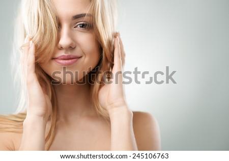 cheerful blond girl straightens her hair - stock photo