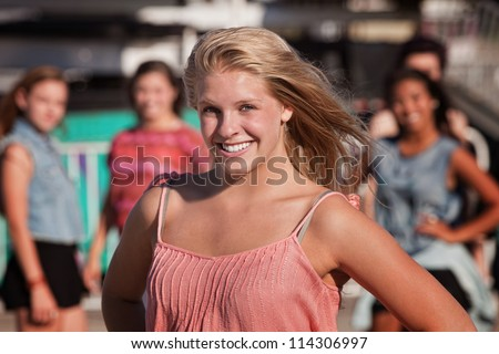 Cheerful blond teenager smiling with friends in background - stock photo