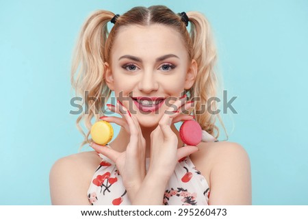 Cheerful blond woman crossed her hands. She is holding two brownies in them and touching her cheeks. The lady is smiling childishly. Isolated on blue background - stock photo