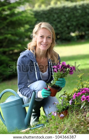 Cheerful blond woman planting flowers in garden - stock photo