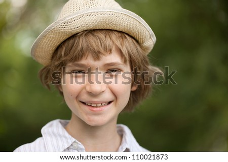 Cheerful blonde boy in a wicker hat - stock photo