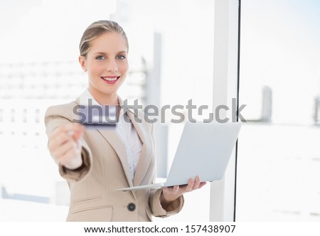 Cheerful blonde businesswoman in bright office showing credit card holding laptop - stock photo