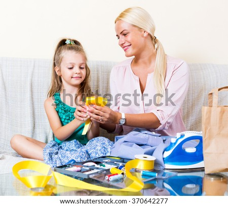 Cheerful blonde mother and little daughter working with textile indoors - stock photo