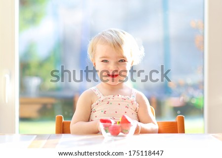 Cheerful blonde toddler girl in summer dress eating strawberries sitting indoors in the sunny kitchen next to a big window with garden view - stock photo