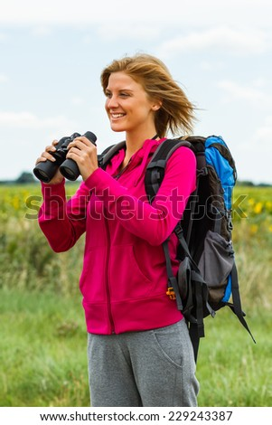 Cheerful blonde woman is standing in the nature and holding binoculars,Enjoying nature with binoculars - stock photo