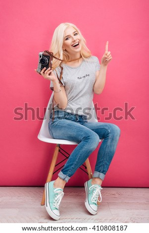 Cheerful blonde woman sitting on the chair with photo camera on pink background - stock photo