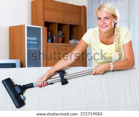 Cheerful blonde young girl hoovering in living room and smiling - stock photo