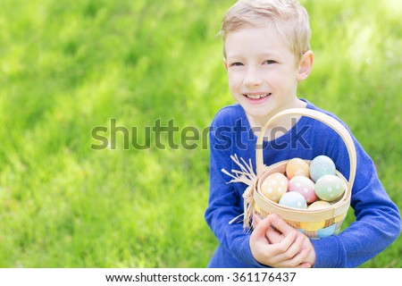cheerful boy holding basket full of colorful easter eggs standing on the grass in the park after egg hunt - stock photo