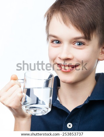 Cheerful boy holding cup of water on white background - stock photo