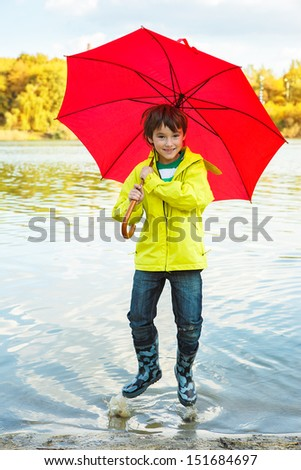 Cheerful boy hopping in water with a red umbrella  - stock photo