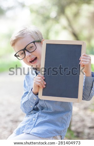 cheerful boy in glasses holding empty blackboard, ready for school - stock photo