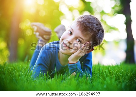 cheerful boy laying on the green grass - stock photo