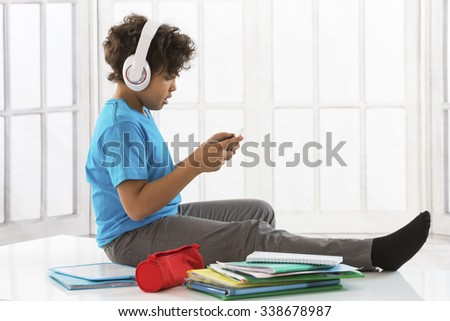 Cheerful boy listening to  Music with the Books  arround him  - stock photo