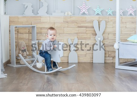 Cheerful boy Toddler baby swinging on a rocking chair in the shape of a horse. - stock photo