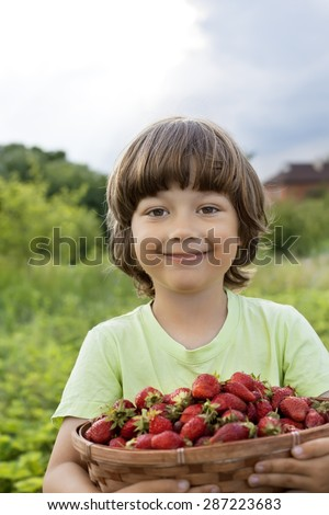 cheerful boy with basket of berries - stock photo