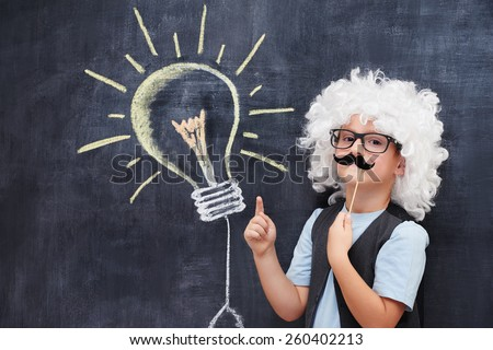 Cheerful boy with fake mustache and Einstein  wig point on bulb visualized on the blackboard - stock photo