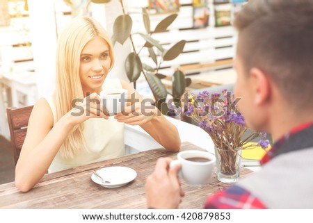 Cheerful boyfriend and girlfriend resting in cafe - stock photo
