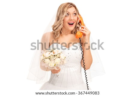 Cheerful bride holding a wedding bouquet and talking on telephone isolated on white background - stock photo