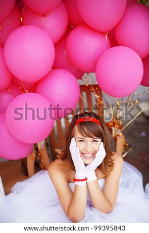 Cheerful bride of 60s style posing with bunch of balloons - stock photo