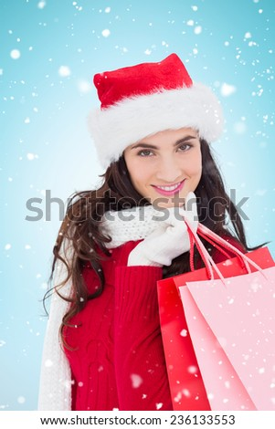Cheerful brunette in winter wear holding shopping bags against blue background with vignette - stock photo