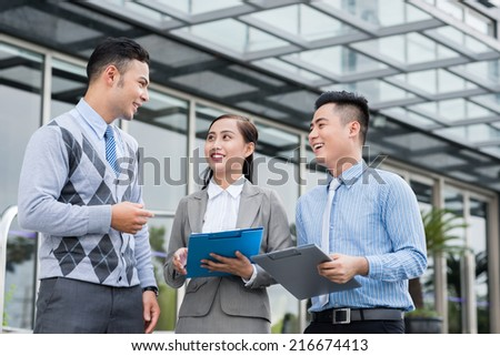 Cheerful business colleagues talking outdoors - stock photo