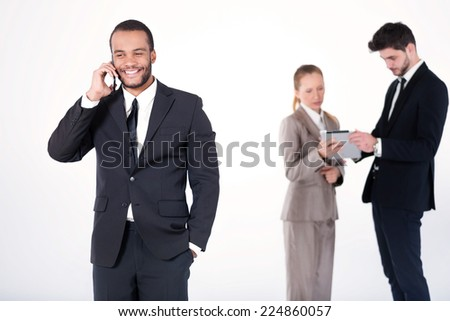Cheerful business conversation. Successful and smiling African businessman talking on cell phone while his colleagues are working on a tablet in the background on a gray background - stock photo