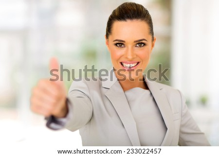 cheerful business executive giving thumb up in office - stock photo