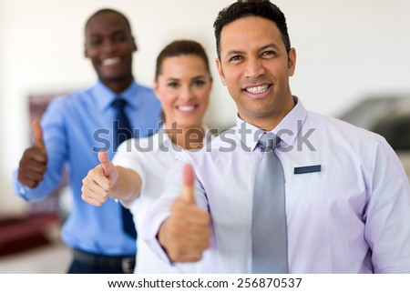 cheerful business group giving thumbs up - stock photo