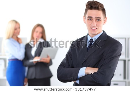 Cheerful business man in office with colleagues in the background, sturt-up team - stock photo