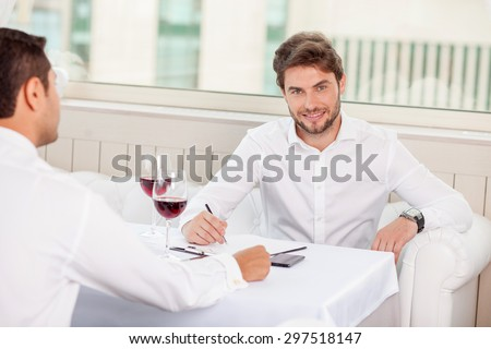 Cheerful business partners are discussing a new project. They are sitting at the table and drinking wine. The man is smiling and writing down main ideas. He is looking at the camera with joy - stock photo