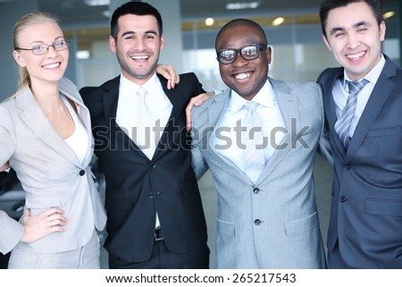 Cheerful business partners in suits looking at camera - stock photo
