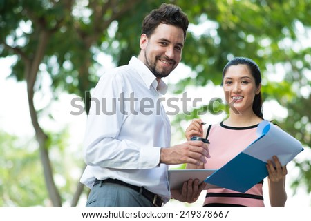 Cheerful business people discussing financial documents outdoors - stock photo