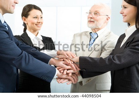Cheerful business people joining their hands - stock photo
