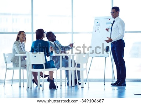 Cheerful business people looking at successful specialist explaining new project at board - stock photo