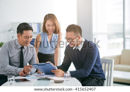 Cheerful business people working with documents together - stock photo