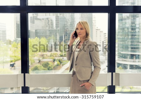 Cheerful business woman on mobile phone at modern office. Buildings background - stock photo