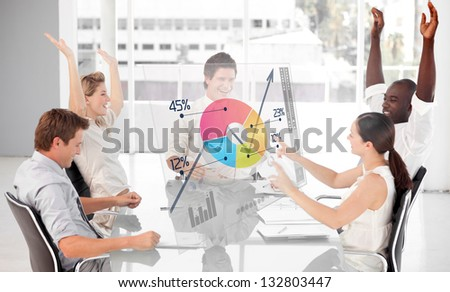 Cheerful business workers using colorful pie chart interface in a meeting - stock photo