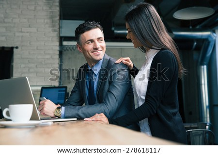 Cheerful businessman and businesswoman using laptop in cafe - stock photo